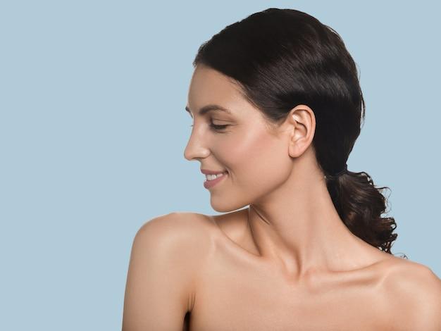 Retrato cosmético del concepto de la piel fresca limpia del pelo largo sano de la mujer hermosa. fondo de color azul
