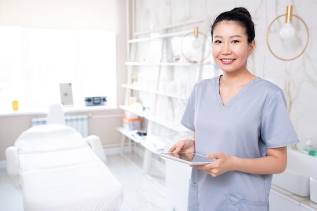 Retrato de cosmetóloga asiática atractiva positiva en uniforme médico con tableta en sala de procedimiento limpio