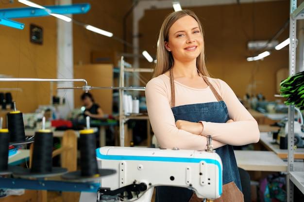 Retrato de una costurera de pie en el lugar de trabajo y mirando a la cámara