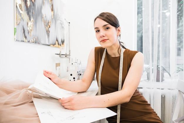 Retrato de una costurera sonriente sosteniendo boceto de moda