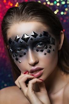 Retrato creativo de una morena con ojos negros y pedrería