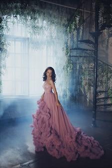 Retrato creativo de una mujer de moda en un hermoso vestido romántico largo rosa