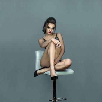 Retrato cuadrado de dama glamour con labios rojos y peinado hermoso se sienta en la silla de cuero blanco en lencería de encaje gris en estudio