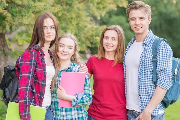Retrato de cuatro estudiantes en parque