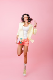 Retrato de cuerpo entero de la adorable joven hispana en pantalones cortos de color rosa saltando con una sonrisa. chica patinadora dichosa en zapatos deportivos divirtiéndose.