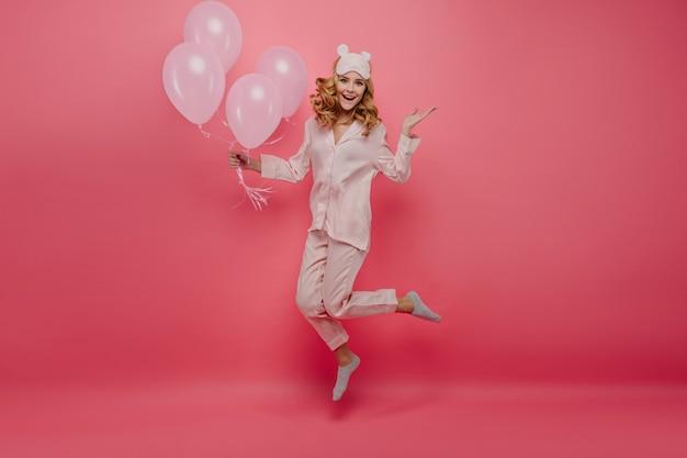 Retrato de cuerpo entero de una agradable cumpleañera en calcetines saltando sobre la pared rosa. linda mujer joven en pijama y antifaz divirtiéndose con globos de helio.