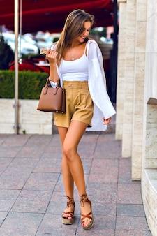 Retrato de cuerpo entero al aire libre de impresionante modelo morena bronceada delgada con pantalones cortos de lino beige, bolso de lujo de cuero caramelo, camisa blanca y accesorios dorados, caminando por las calles de parís.