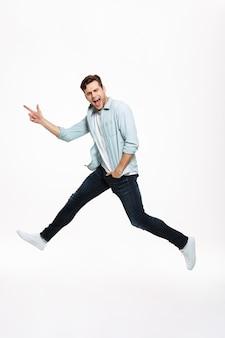 Retrato de cuerpo entero de un alegre hombre feliz saltando