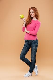 Retrato de cuerpo entero de una alegre niña bonita pelirroja con manzana