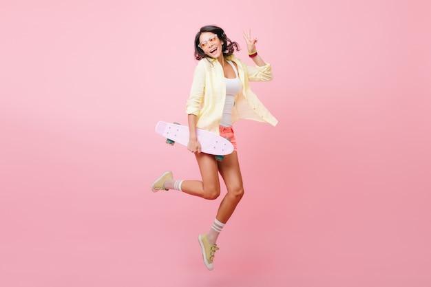 Retrato de cuerpo entero de alegre niña morena saltando con patineta. increíble dama hispana en traje colorido bailando, sosteniendo longboard y riendo.
