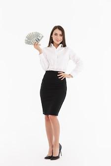 Retrato de cuerpo entero de una atractiva joven empresaria vistiendo ropa formal que se encuentran aisladas sobre una pared blanca, mostrando billetes de dinero, celebrando