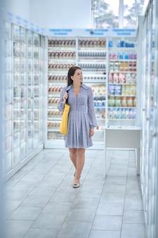 Retrato de cuerpo entero de una atractiva mujer caucásica de mediana edad de pelo oscuro caminando por las vitrinas de la farmacia