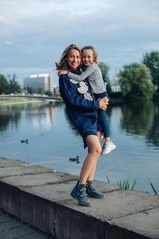 Retrato de cuerpo entero de atractiva mujer caucásica rubia sonriente en vestido azul y botas abrazando a su encantadora hija sonriente en sus brazos de pie junto al lago con patos en el parque de noche.