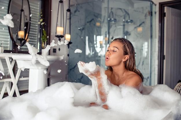 Retrato de cuerpo entero de una bella mujer morena que sopla espuma mientras toma un baño relajante