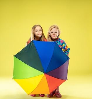 Un retrato de cuerpo entero de un brillante chicas de moda en un impermeable sosteniendo un paraguas de colores del arco iris en la pared amarilla del estudio