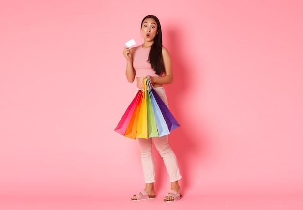 Retrato de cuerpo entero de una chica asiática bonita emocionada en ropa de moda
