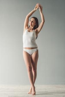 Retrato de cuerpo entero de una chica atractiva en ropa interior blanca.