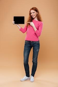 Retrato de cuerpo entero de una chica pelirroja satisfecha señalando con el dedo a la tableta digital