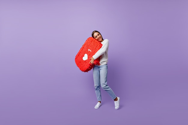 Retrato de cuerpo entero de chica refinada obsesionada con las redes sociales. blogger femenina bien vestida de pie en púrpura