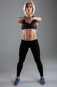 Retrato de cuerpo entero de una deportista adulta muscular concentrada