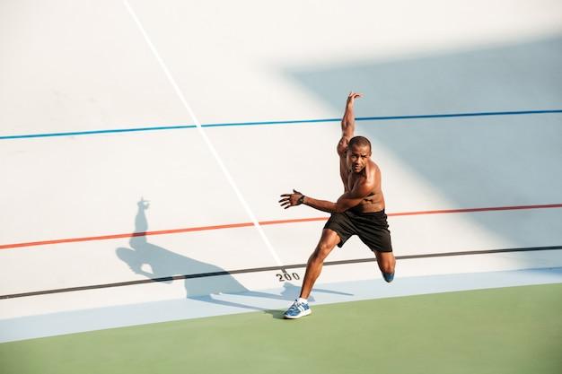 Retrato de cuerpo entero de un deportista concentrado medio desnudo