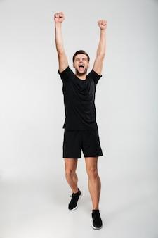 Retrato de cuerpo entero de un deportista divertido feliz celebrando el éxito