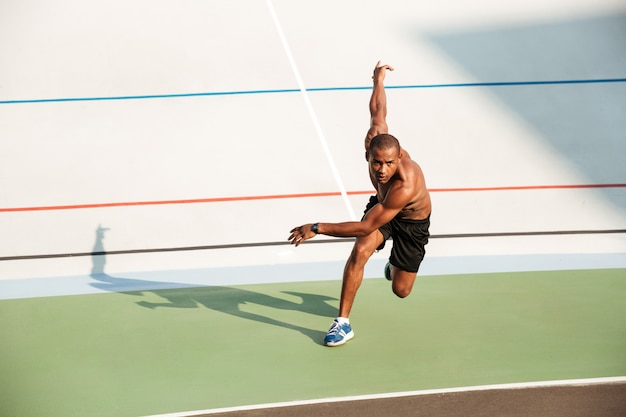 Retrato de cuerpo entero de un deportista motivado medio desnudo