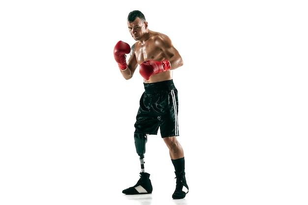 Retrato de cuerpo entero de deportista musculoso con prótesis de pierna, espacio de copia. boxeador masculino en guantes rojos. disparo aislado en la pared blanca.