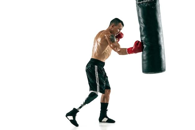 Retrato de cuerpo entero de deportista musculoso con prótesis de pierna, espacio de copia. boxeador masculino en guantes rojos entrenando y practicando. aislado en la pared blanca. concepto de deporte, estilo de vida saludable.