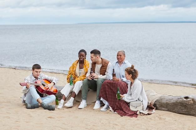 Retrato de cuerpo entero de diverso grupo de amigos en la playa en otoño tocando la guitarra y bebiendo cerveza ...