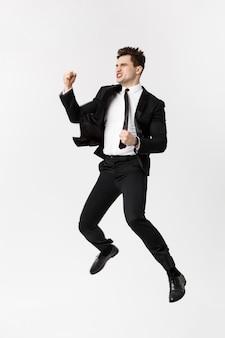 Retrato de cuerpo entero divertido empresario alegre saltando en el aire sobre fondo gris