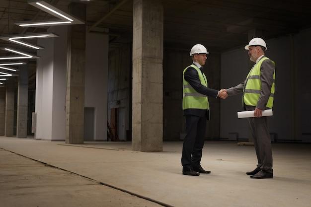 Retrato de cuerpo entero de dos empresarios exitosos dándose la mano mientras está de pie en el sitio de construcción,