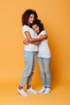 Retrato de cuerpo entero de dos hermanas africanas felices