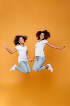 Retrato de cuerpo entero de dos hermanas afroamericanas emocionadas