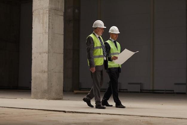 Retrato de cuerpo entero de dos hombres de negocios con cascos y planes mientras camina en el sitio de construcción en el interior,