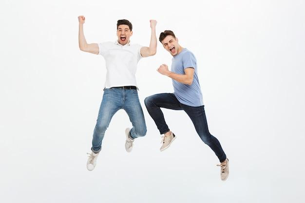Retrato de cuerpo entero de dos jóvenes excitados saltando