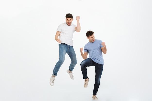 Retrato de cuerpo entero de dos jóvenes felices saltando