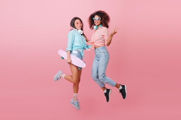 Retrato de cuerpo entero de dos mujeres deportivas saltando y sonriendo. chica glamorosa patinadora en camisa azul divirtiéndose con una amiga africana en zapatos negros.