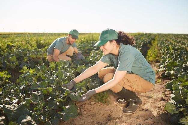 Retrato de cuerpo entero de dos trabajadores sonrientes en la plantación al aire libre, se centran en la mujer joven inspeccionando las hojas en primer plano, espacio de copia