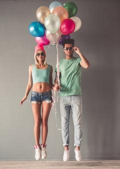 Retrato de cuerpo entero de la elegante joven pareja en gafas de sol.