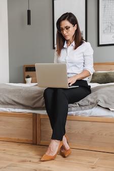 Retrato de cuerpo entero de una empresaria adulta seria en traje formal escribiendo en la computadora portátil mientras está sentado en la cama en el apartamento