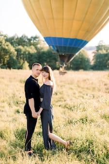 Retrato de cuerpo entero de una encantadora pareja joven vestida de negro, abrazándose y disfrutando de la caminata de verano en el campo, esperando su recorrido en globo aerostático