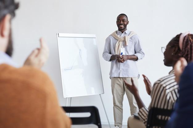 Retrato de cuerpo entero de un entrenador de negocios afroamericano hablando con la audiencia en la conferencia o seminario educativo mientras está de pie junto a la pizarra y sonriendo, copie el espacio