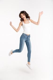 Retrato de cuerpo entero de una excitada mujer vestida con una camiseta sin mangas