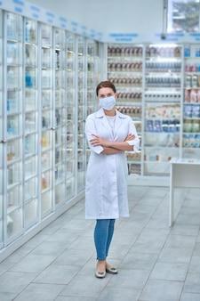 Retrato de cuerpo entero de un farmacéutico en una máscara médica de pie entre estantes con diferentes productos sanitarios