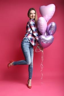 Retrato de cuerpo entero de feliz bella mujer joven con globos de colores