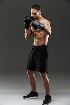 Retrato de cuerpo entero de un fuerte deportista musculoso sin camisa