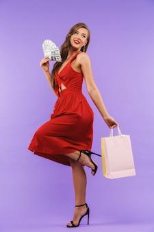 Retrato de cuerpo entero de glamour mujer con vestido rojo sonriendo sosteniendo abanico de dinero y bolsas de papel
