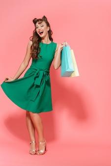 Retrato de cuerpo entero de una hermosa joven pin-up vestida con un vestido que se encuentran aisladas, llevando bolsas de la compra.