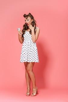 Retrato de cuerpo entero de una hermosa joven pin-up vestida con un vestido que se encuentran aisladas, mediante teléfono móvil